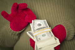 Woman Wearing Mittens Holding Stacks of Money with Red Ribbon Stock Photo