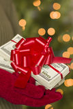 Woman Wearing Mittens Holding Stacks of Money with Red Ribbon Royalty Free Stock Photography
