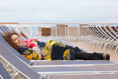 Woman wearing in mittens and plaid lies on lounger. Happy woman wearing in red mittens and plaid lies on lounger at ship deck Stock Photos