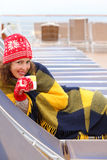 Woman wearing in mittens and plaid lies on lounger. Happy woman wearing in red mittens and plaid lies on lounger at ship deck and drinks hot tea Royalty Free Stock Photo