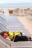 Woman wearing in mittens sleeps on lounger. Woman wearing in red mittens and plaid sleeps on lounger at ship deck Stock Images
