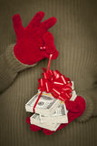 Woman Wearing Mittens Unwrapping Red Bow on Stack of Money Royalty Free Stock Photos