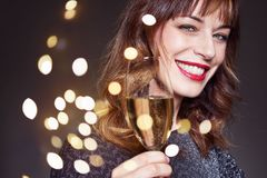 Woman wearing night party dress with a glass of champagne on dark background. Lady with long curly hair and perfect teeth celebrat. Ing and smiling royalty free stock photography