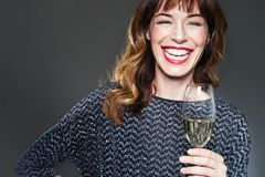Woman wearing night party dress with a glass of champagne on dark background. Lady with long curly hair and ref lips celebrating. And laughing stock images