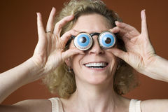 Woman wearing novelty eyeglasses. Portrait of a woman clowning and wearing novelty eyeglasses Royalty Free Stock Image