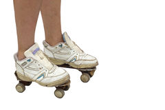 Woman wearing old sport shoes and rusty roller skates,. Legs of a woman wearing old sport shoes and rusty roller skates Royalty Free Stock Images