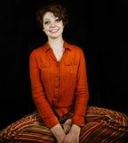Woman wearing orange shirt. And striped pants sitting cross-legged Royalty Free Stock Photo