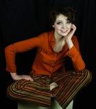 Woman wearing orange shirt. And striped pants sitting cross-legged Stock Images