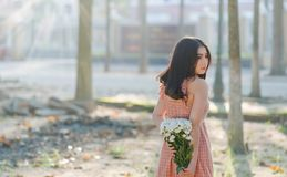 Woman Wearing Orange Sleeveless Dress Holding a Bouquet of Flowers Stock Photography
