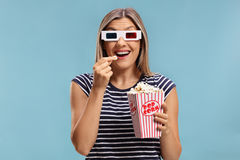 Woman wearing a pair of 3D glasses and eating popcorn Royalty Free Stock Photo