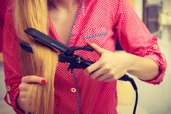 Woman wearing pajamas curling her hair Stock Images