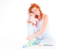 Woman wearing pajamas with a soft toy. Royalty Free Stock Photo