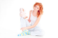 Woman wearing pajamas with a soft toy. Stock Photography