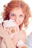 Woman wearing pajamas with a soft toy. Royalty Free Stock Photos