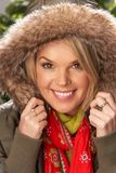 Woman Wearing Parka Coat And Scarf In Studio Stock Image