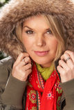 Woman Wearing Parka Coat And Scarf In Studio. Fashionable Woman Wearing Parka Coat And Scarf In Studio In Front Of Christmas Tree Stock Photos