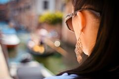 Woman Wearing Pendant Earrings and Sunglasses Royalty Free Stock Images