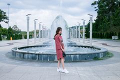 Woman Wearing Pink Crew-neck Long-sleeved Midi Dress Standing Concrete Outdoor Fountain Stock Photo