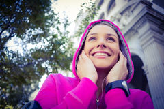 A woman wearing a pink jacket putting her headphones Royalty Free Stock Image