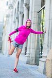 A woman wearing a pink jacket stretching Royalty Free Stock Images