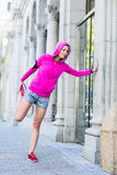A woman wearing a pink jacket stretching Royalty Free Stock Photos