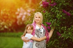 Mother and Daughter in the park with lilacs. Young pregnant woman in white dress and child looking in the camera and smiling. royalty free stock photography