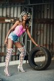 Woman Wearing Pink Spaghetti Strap Top and Blue Denim Shorts Holding Vehicle Tire royalty free stock images