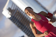 Woman wearing pink sports vest, jogging in city, listening to MP3 player strapped to arm, smiling, focus on foreground (tilt) Royalty Free Stock Photos