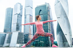 Woman wearing pink sportswear in Warrior two pose Royalty Free Stock Photography
