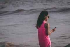 Woman Wearing Pink Tank Top Standing Near Sea Shore stock photography