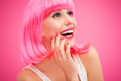 Woman wearing pink wig and laughing. Woman wearing wig over pink background Royalty Free Stock Images