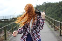 Woman Wearing Plaid Button-up Sport Shirt While Holding Black Hood royalty free stock images