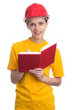 Woman wearing protect helmet and making notes. In a notebook Royalty Free Stock Photography