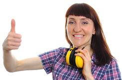 Woman wearing protective headphones and showing thumbs up Stock Photo