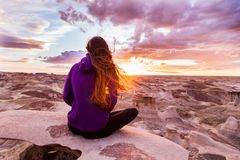 Woman Wearing Purple Hooded Jacket Sitting on Rock stock images