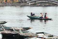 Woman wearing purple long arm t-shirt and conical hat rowing boat by her feet with tourists on the boat on the river at Trang An. Woman wearing purple long arm Stock Photography