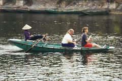 Woman wearing purple long arm t-shirt and conical hat rowing boat by her feet with tourists on the boat on the river at Trang An. Woman wearing purple long arm Royalty Free Stock Image