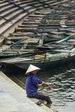 Woman wearing purple shirt, conical hat carry wash her feet in the river with empty rowing boats in the background at Trang An. Grottoes in Ninh Binh, Vietnam Stock Images
