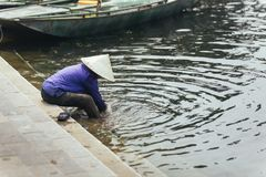 Woman wearing purple shirt, conical hat carry wash her feet in the river at Trang An Grottoes in Ninh Binh, Vietnam.  Stock Photos
