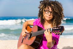 Woman Wearing Purple Shirt Playing Brown Classical Guitar While Sitting Near Shoreline With Water Splashing Background in Daytime Royalty Free Stock Image