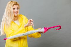 Woman wearing raincoat closing umbrella. End of rainy weather. Woman wearing yellow raincoat holding and closing umbrella Royalty Free Stock Photography