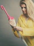 Woman wearing raincoat closing umbrella Royalty Free Stock Photography