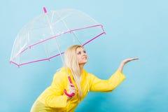 Woman wearing raincoat holding umbrella checking weather. Blonde woman wearing yellow raincoat holding transparent umbrella checking weather if it is raining Royalty Free Stock Image