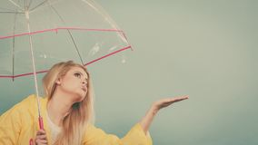 Woman wearing raincoat holding umbrella checking weather. Blonde woman wearing yellow raincoat holding transparent umbrella checking weather if it is raining Royalty Free Stock Images