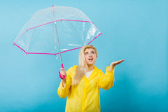 Woman wearing raincoat holding umbrella checking weather Royalty Free Stock Images