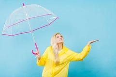 Woman wearing raincoat holding umbrella checking weather Stock Photo