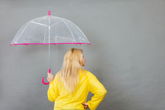 Woman wearing raincoat holding umbrella checking weather Royalty Free Stock Photography