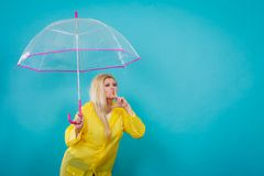 Woman wearing raincoat holding umbrella checking weather. Blonde woman wearing yellow raincoat holding transparent umbrella checking weather if it is raining Stock Photography