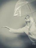 Woman wearing raincoat holding umbrella checking weather. Woman wearing raincoat holding transparent umbrella checking weather if it is raining Royalty Free Stock Images