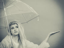 Woman wearing raincoat holding umbrella checking weather. Woman wearing raincoat holding transparent umbrella checking weather if it is raining Stock Images